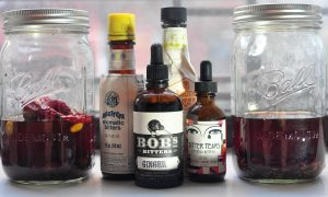2 jars of homemade bitters with several bottles of store-bought bitters in the middle