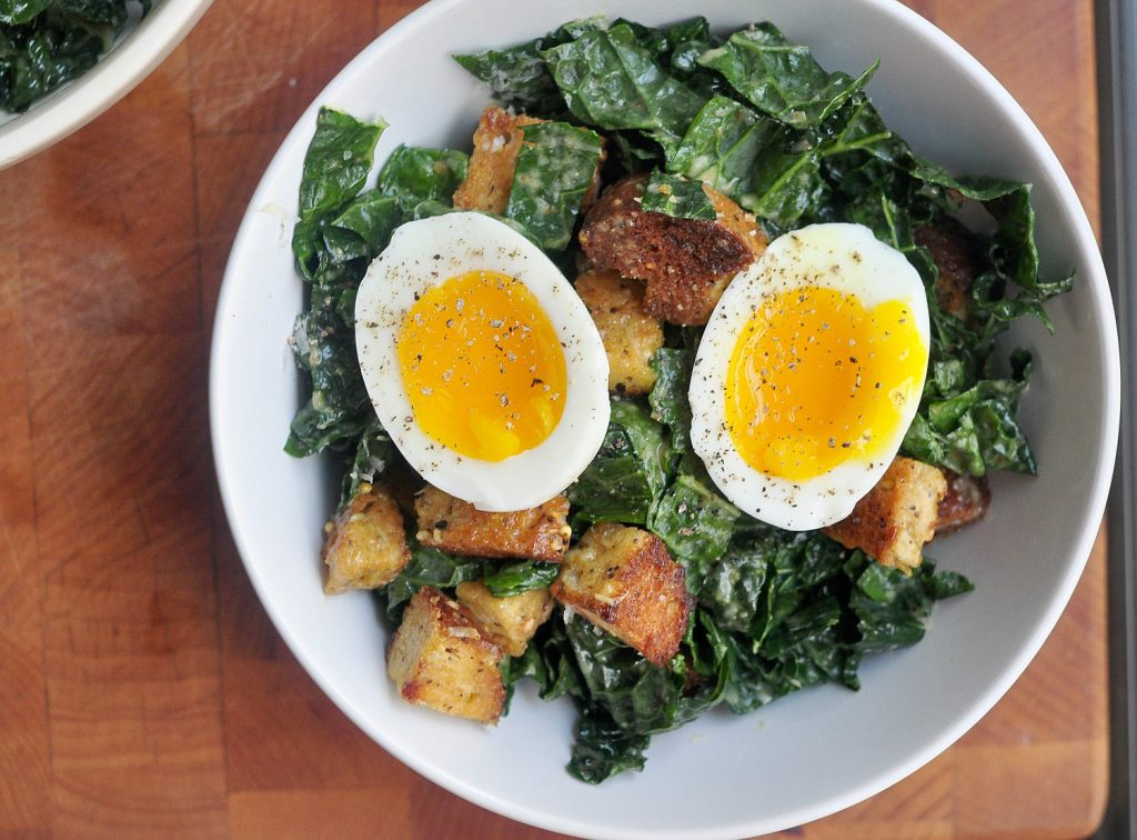 Kale Caesar salad with a two halves of a soft boiled egg on top