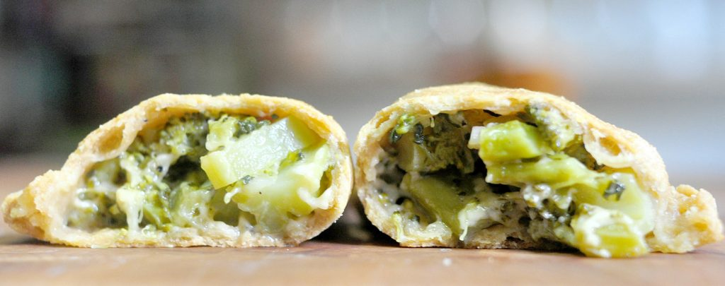 cross section of an empanada filled with broccoli and cheddar