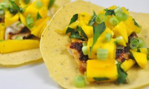 chipotle glazed tilapia tacos topped with mango and cilantro on a white plate