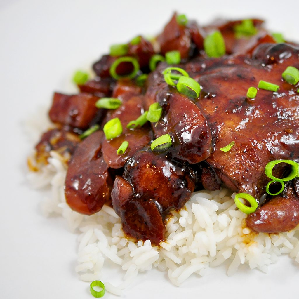 Chicken Adobo over a pile of white rice on a white background with scallions sprinkled on top