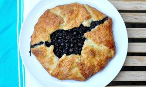 blueberry crostata on a white plate with blue striped dish towel