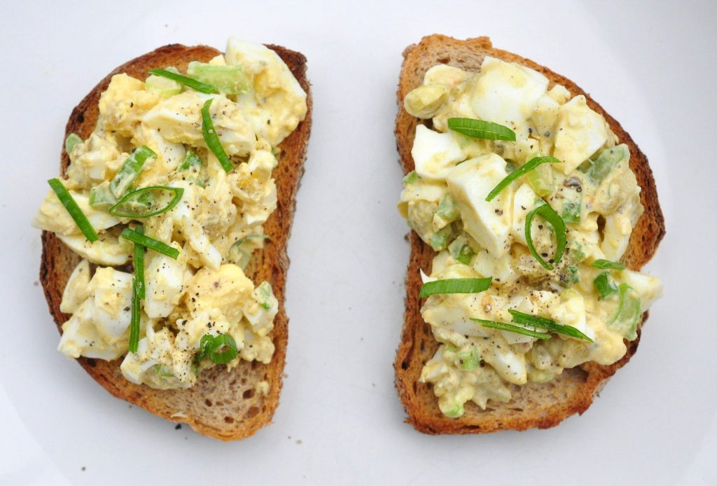 green chile egg salad topped on 2 pieces of toast