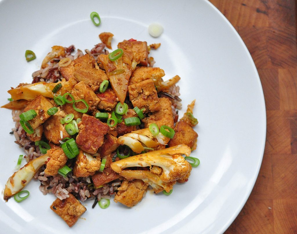 white plate with gochujang tofu and cauliflower on a bed of rice
