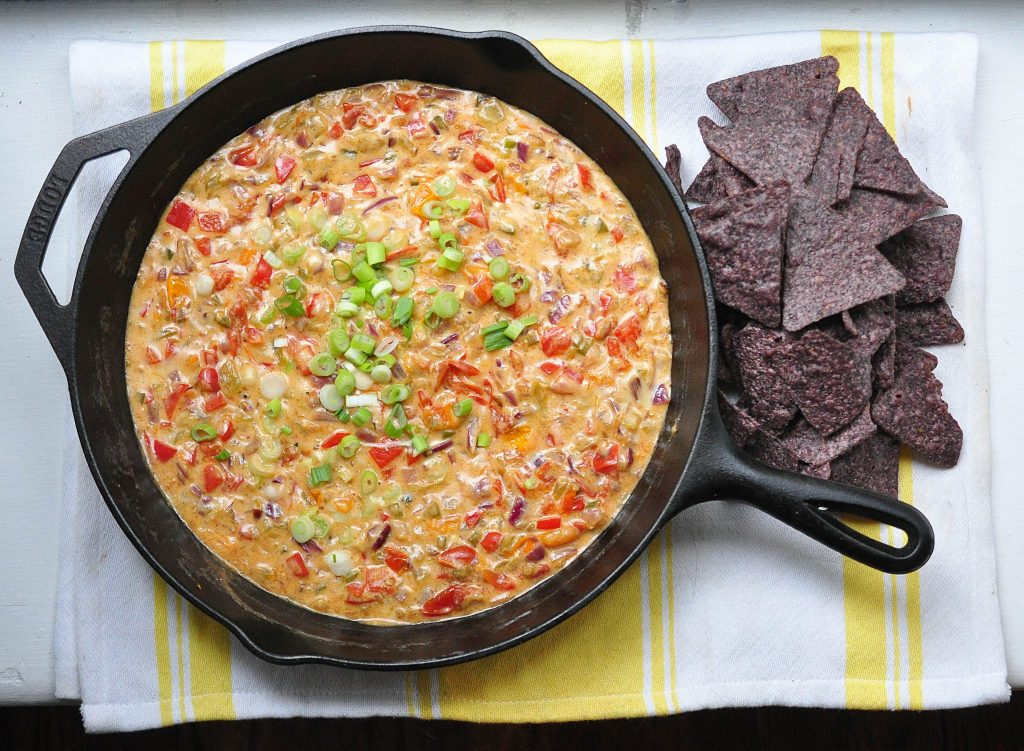queso fundido in a cast iron pan with tortilla chips on the side