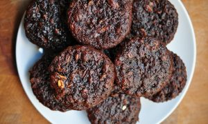 chocolate zucchini muffins piled on a white plate