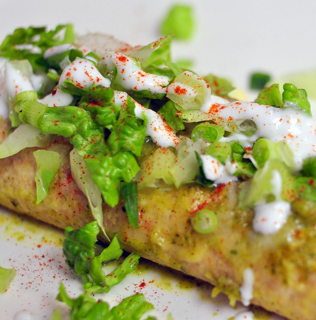 black bean enchiladas topped with melted cheddar, lettuce and sour cream