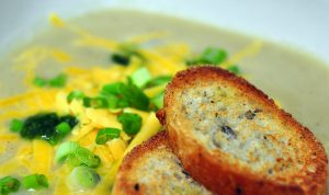 cauliflower soup topped with cheddar and scallions with sliced baguette