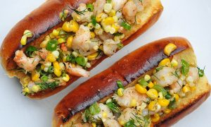 2 overstuffed hot dog rolls full of shrimp, corn and vegetables