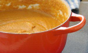 orange pot with sweet potato soup inside