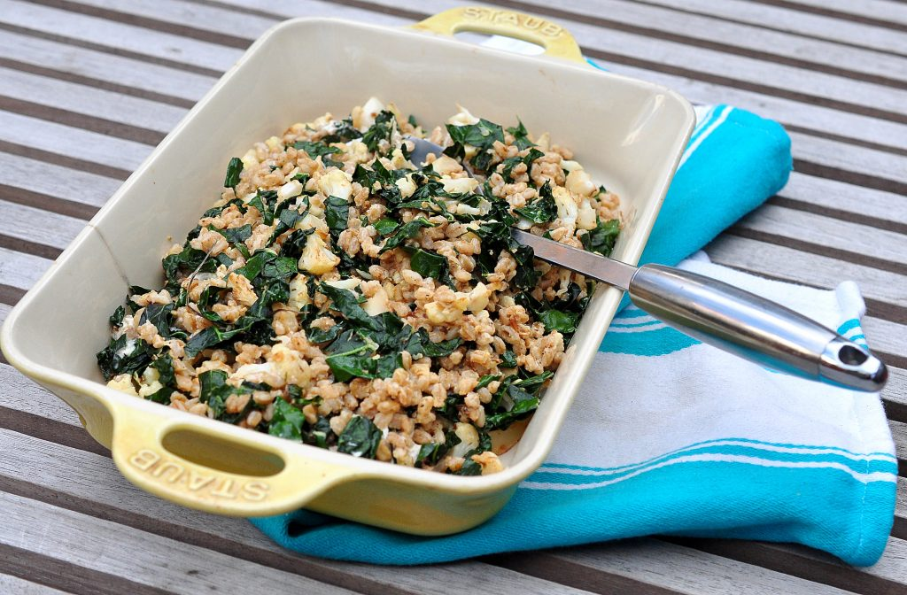 platter of farro salad with cauliflower and kale on dish towel with serving spoon