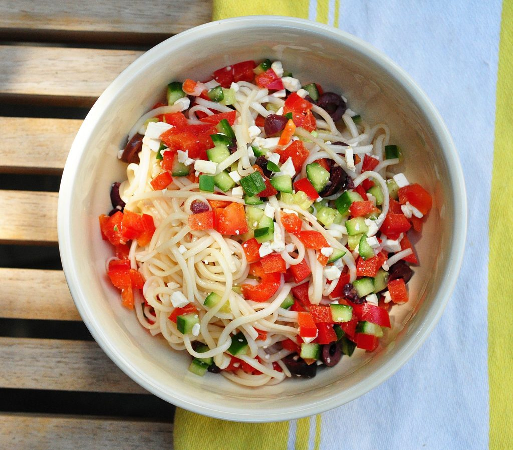 Noodles with Greek Salad ingredients in a bowl on a yellow striped dish towel