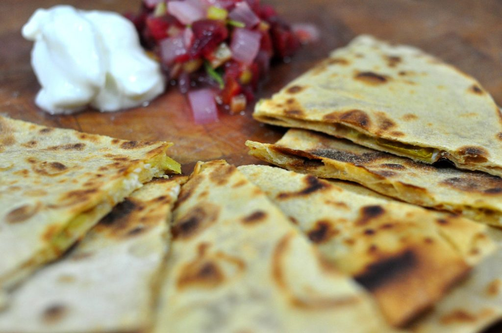 green chile and cheddar quesadillas cut into triangles and served with salsa and sour cream