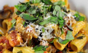eggplant tomato pasta piled in a bowl and topped with cheese and basil