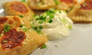 pan-fried pierogi with sour cream and scallions
