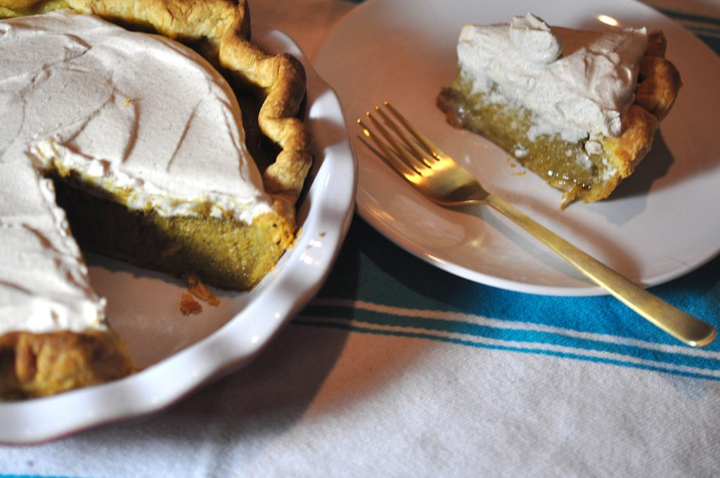 Pumpkin pie with a slice removed and a gold fork