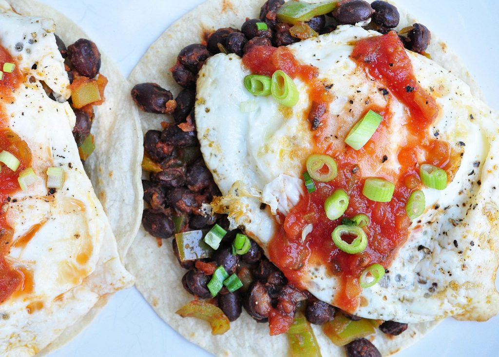 tortillas topped with beans, a fried egg, salsa and scallions