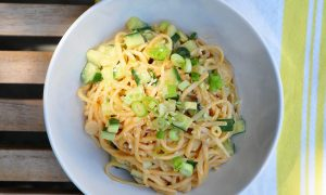 white bowl with sesame noodles topped with cucumbers and scallions