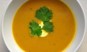 bowl of butternut squash soup with drizzle of sour cream and cilantro leaves