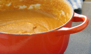 orange pot with sweet potato soup inside