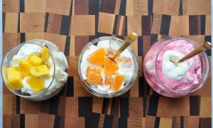 whipped cream with mango, oranges and raspberries in cups with gold spoons