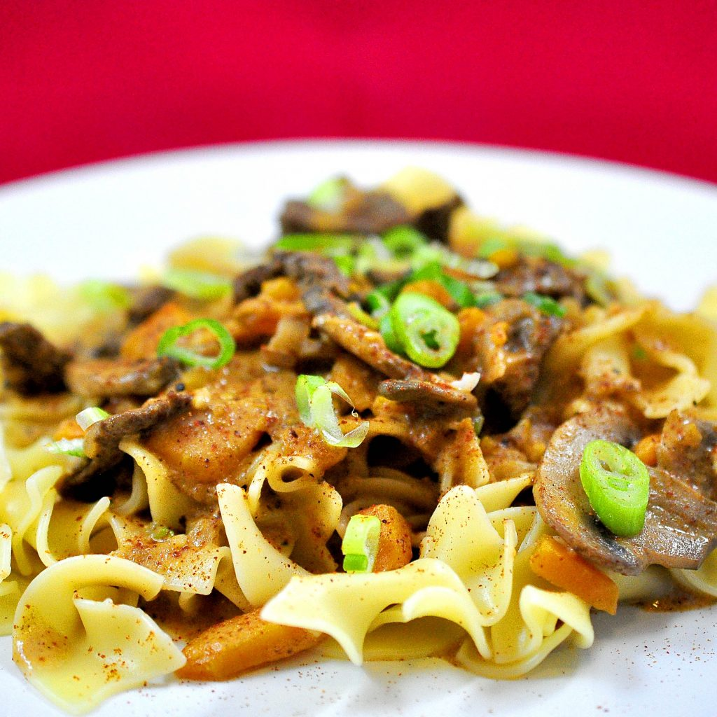 beef and vegetables in a creamy sauce over a pile of egg noodles on a white plate. with a red background