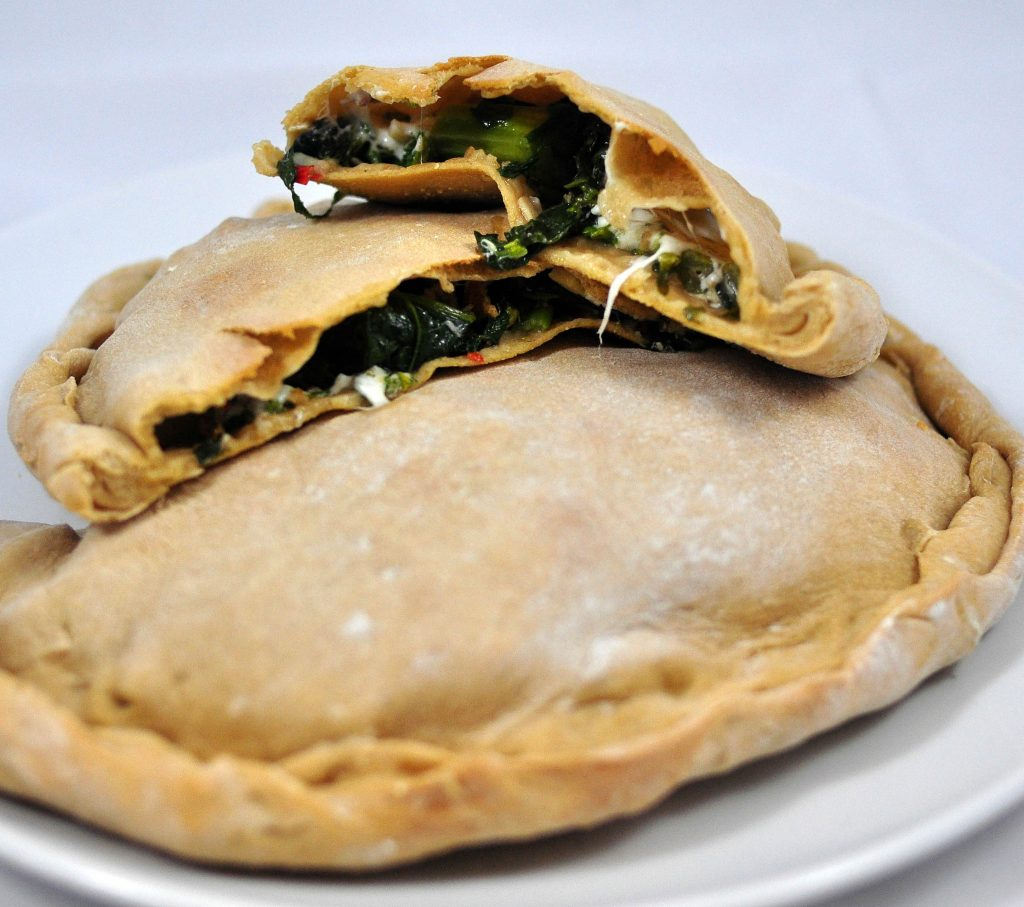 broccoli rabe calzone cut in half laying on top of another calzone