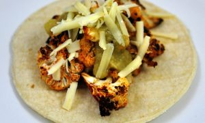 cauliflower tacos with roasted cauliflower rubbed with smoked paprika and topped with cheese and green salsa