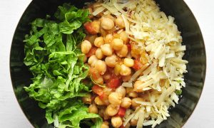black bowl on white background full of chickpeas, cheese and lettuce taco bowl