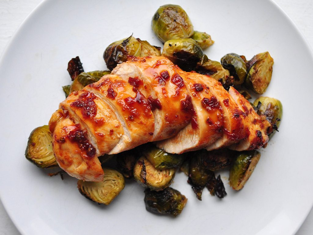 chipotle honey chicken on a bed of brussels sprouts on a white plate