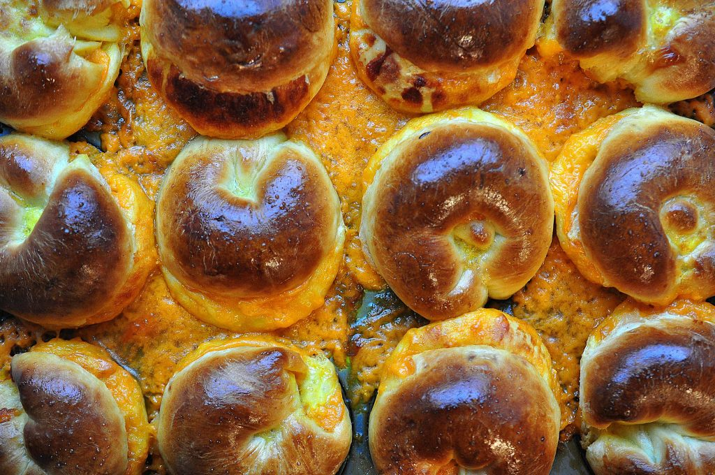 close up of tops of cheese buns in a tray with gooey cheese baked onto the pan