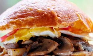 Close up of bun with fried egg, mushroom hash and a glimpse of tomato