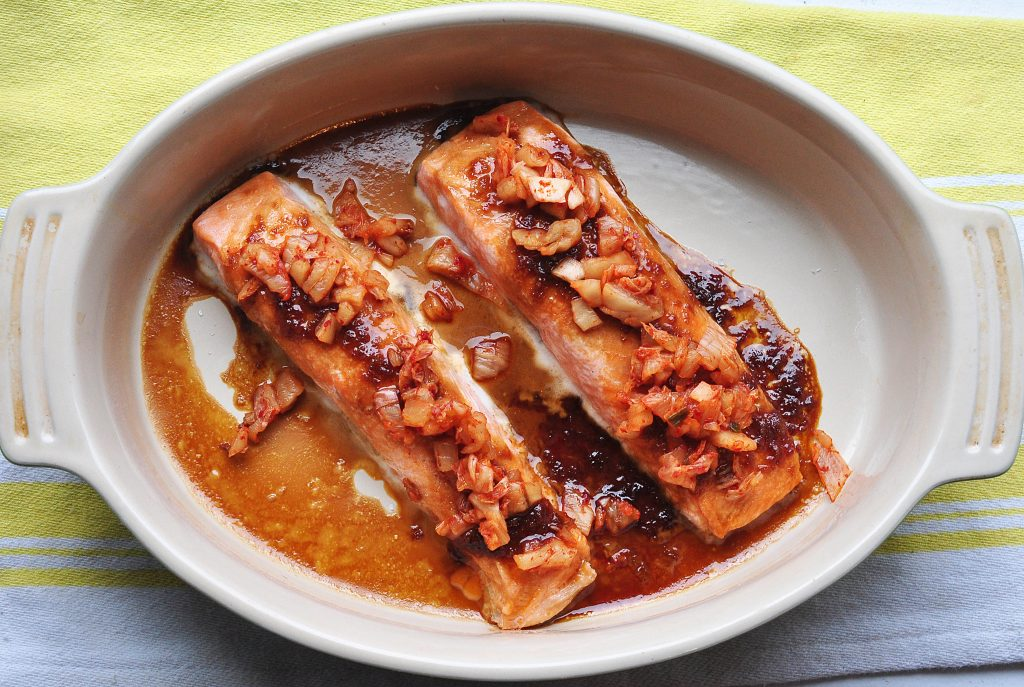two salmon fillets glazed with garlic and soy sauce and topped with chopped kimchi