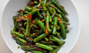 green beans covered in chile paste, garlic and soy sauce piled into a white bowl