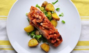 white plate with pile of roasted potatoes and scallions and a fillet of salmon glazed with soy and garlic and topped with kimchi