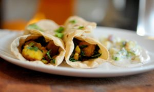 Potato and kale rolled up in a roti with raita on the side and cilantro sprinkled on top.