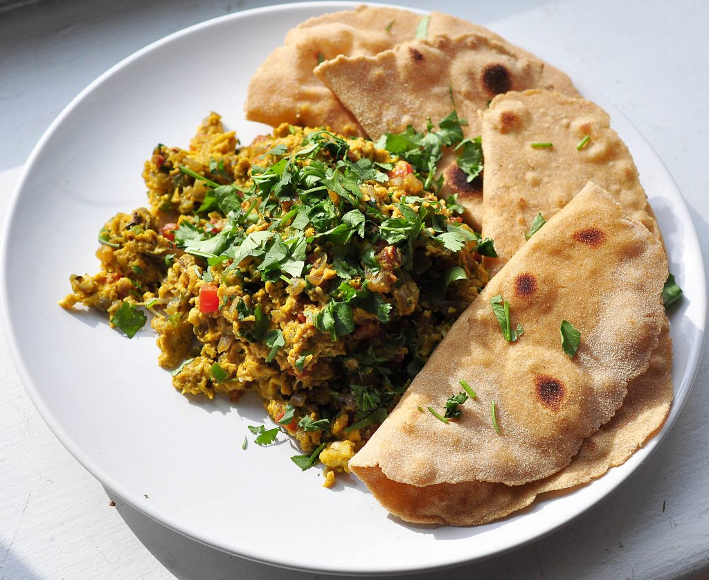 white plate with pile of very yellow scrambled eggs and vegetables with cilantro on top and four pieces of roti