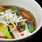 Tofu hot pot, bowl of noodles, tofu and vegetables in a warm ginger-garlic broth