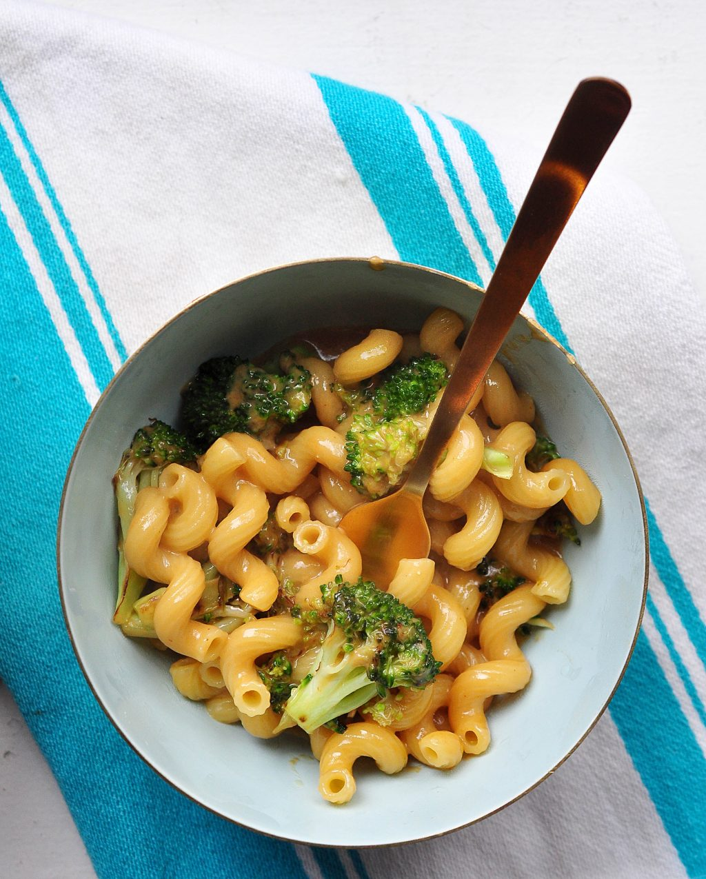 welsh rarebit mac and cheese with broccoli in a bowl with a gold fork
