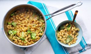 welsh rarebit macaroni and cheese with broccoli in a pot on a teal striped tea towel and in a bowl with a fork