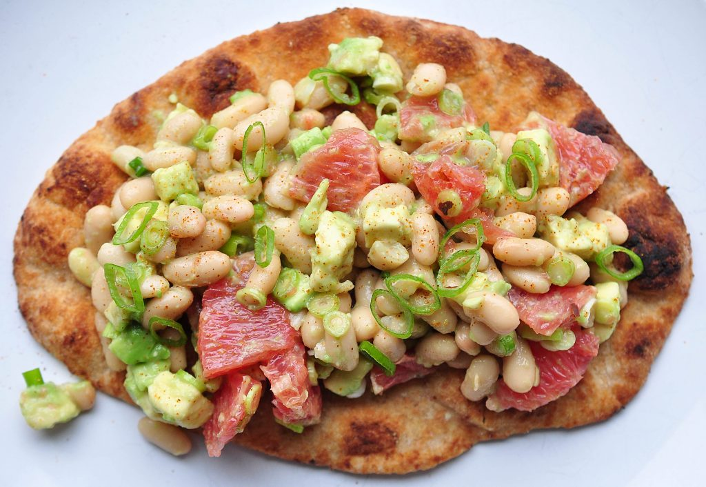 naan bread piled high with avocado, white bean and grapefruit salad