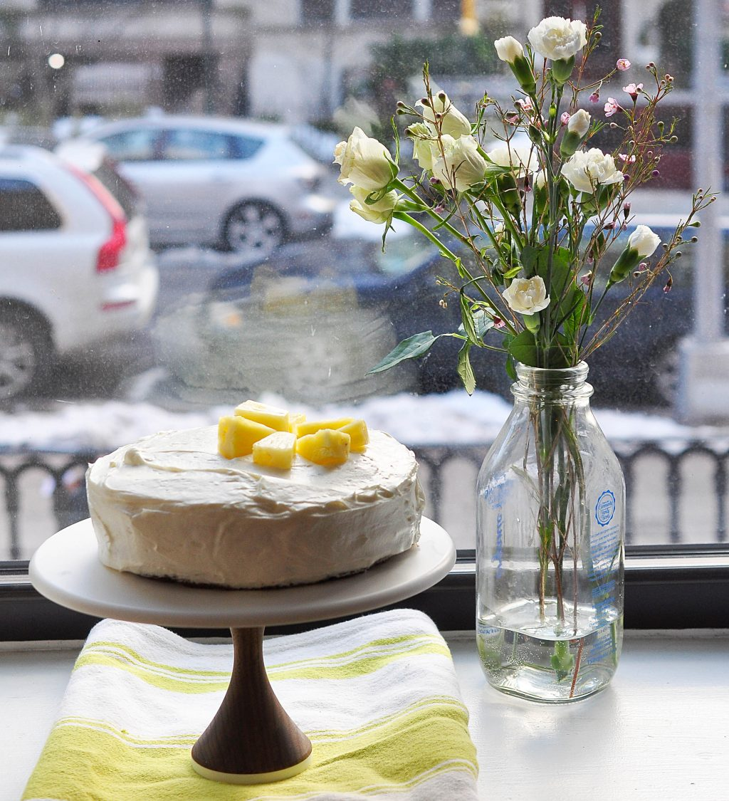 Carrot-pineapple cake on stand by window with flowers