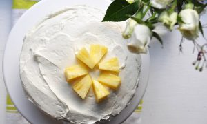 Carrot-pineapple cake with cream cheese frosting from the top with flowers