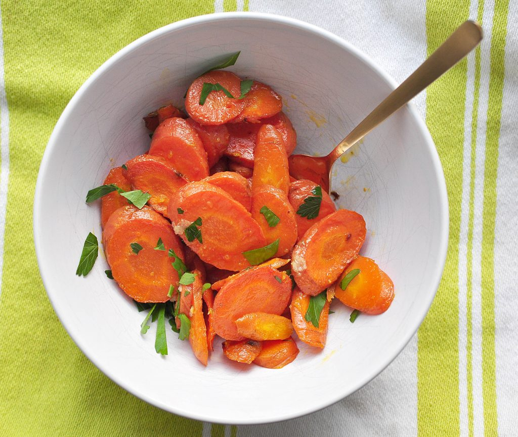 roasted sliced carrots with ginger and butter piled in a white bowl with a light green and white cloth underneath