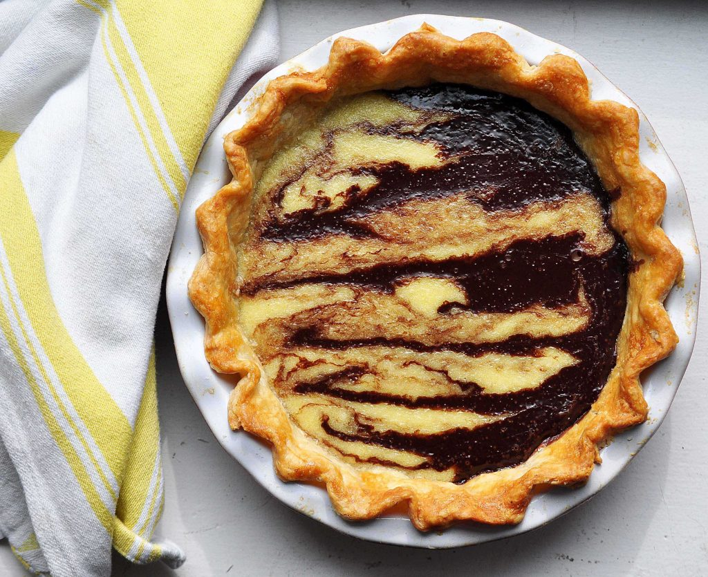 coconut chocolate swirl pie in dish with yellow dish cloth beside
