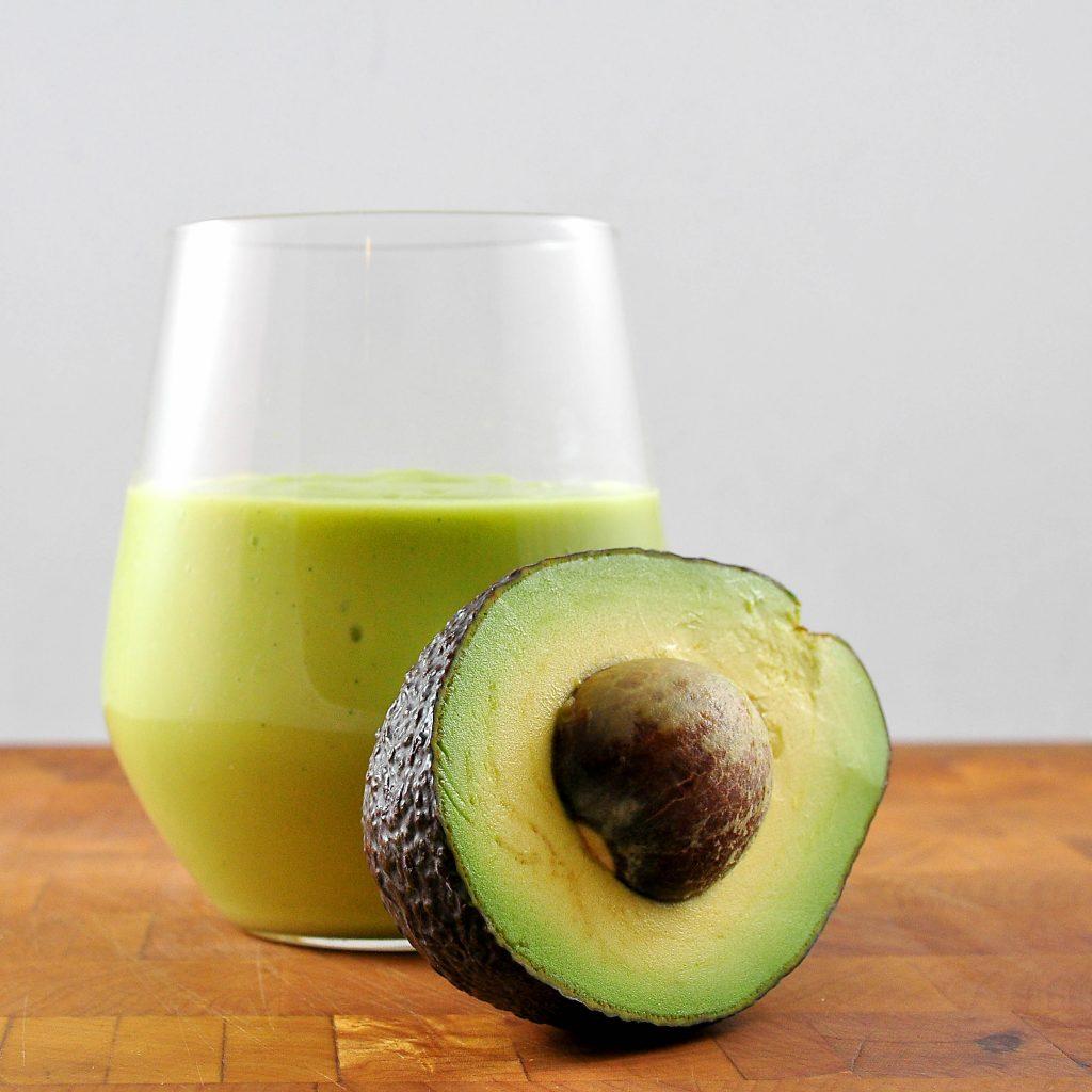 avocado milkshake in glass with half an avocado leaning on it