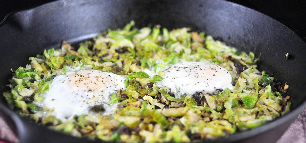 cast iron pan with brussels sprouts hash and eggs