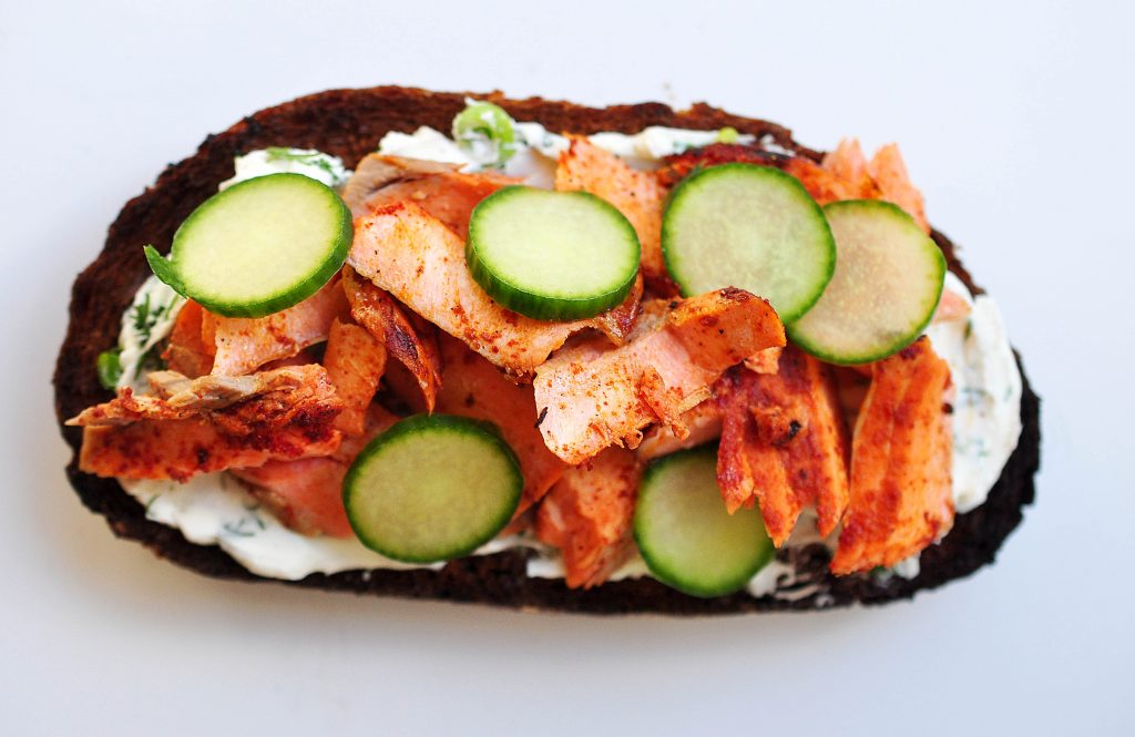 pumpernickel bread with smoked paprika rubbed salmon, cucumbers and dill cream cheese