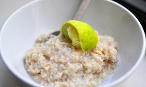 coconut lime oatmeal in a white bowl with a squeezed lime wedge on top