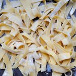 uncooked fresh pasta noodles in a pile tossed with flour